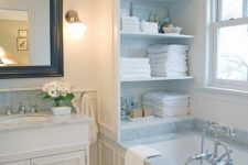19 a cabinet with open shelves placed over the tub is a stylish storage unit you may rock