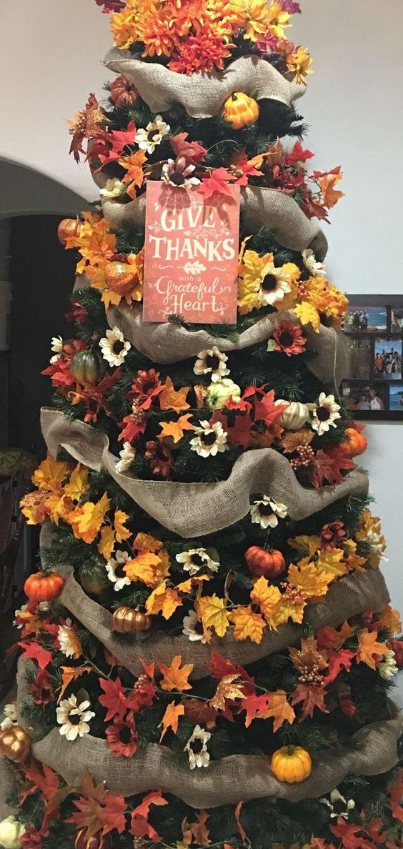 a stylish Thanksgiving tree with burlap ribbons, bright faux blooms and leaves and a chic sign