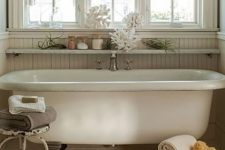 21 a shabby chic coastal bathroom with an open floating shelf over the tub that allows displaying decor