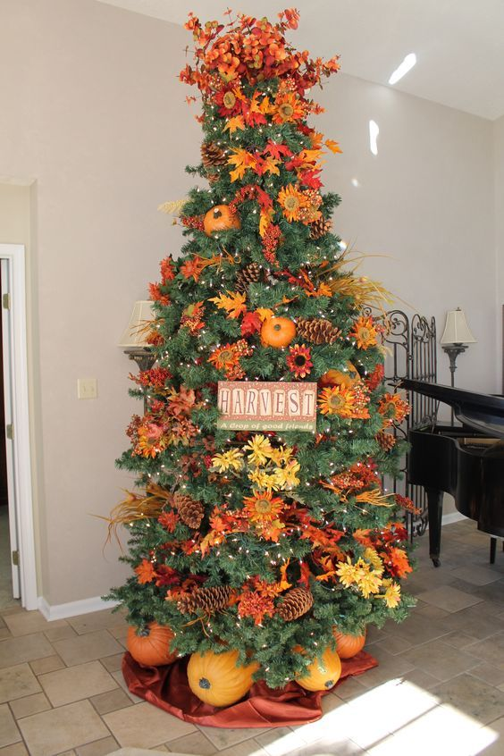 a gorgeous and bright Thanksgiving tree with lights, pinecones, bright faux blooms and leaves, branches, a sign and pumpkins