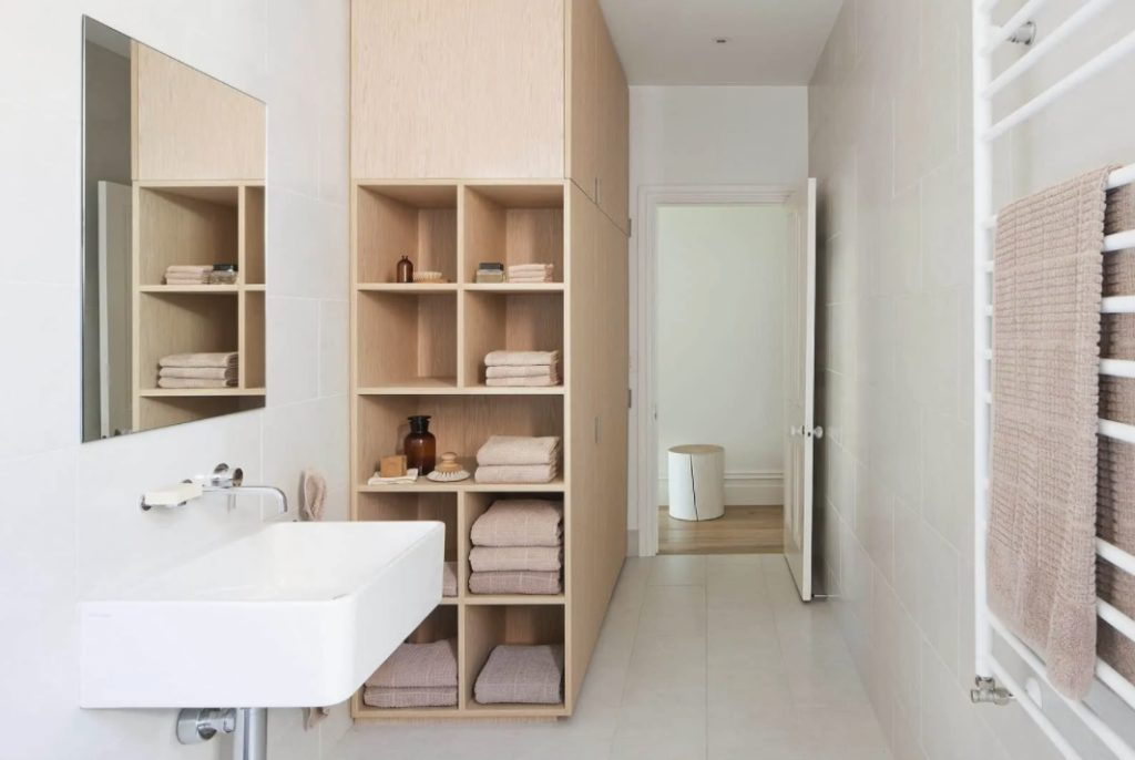 a neutral minimalist bathroom showing off a large cabinet for storage that ends up with open shelving for more comfort