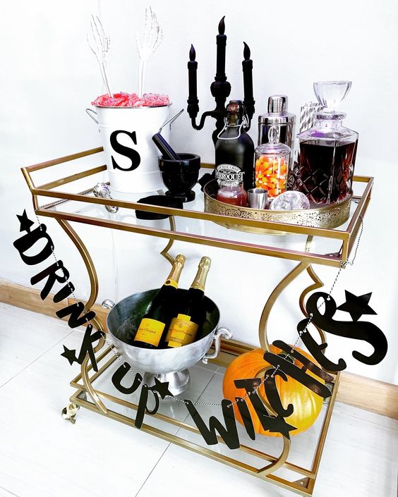 a Halloween drink station with a letter garland, a black candelabra with candles, skeleton hands and elegant drinks and candies