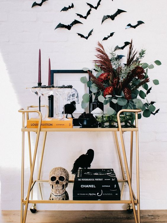 a Halloween bar cart with an embellished skull, a dark floral arrangement, burgundy candles and bats over the cart