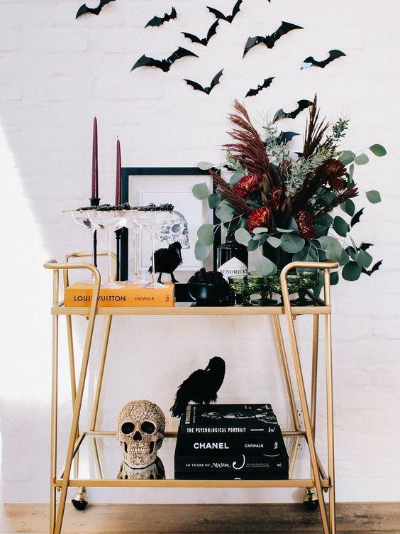 a Halloween bar cart with an embellished skull, a dark floral arrangement, burgundy candles and bats over the cart