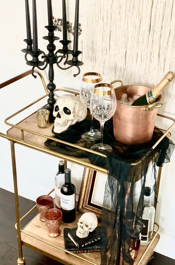 a Halloween bar cart with skulls, a black candelabra with black candles, black cheesecloth, copper barware and elegant glasses