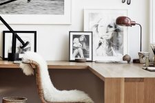 a Scandinavian home office nook with a floating corner desk, a gallery wall, a rattan chair and a basket plus some faux fur
