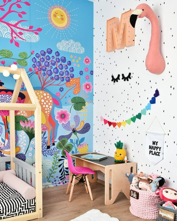 a beautiful and bold kid's room with a bright paitned wall, faux taxidermy, bold garlands and toys and a hot pink chair