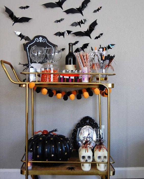 a bold Halloween bar cart with a bright pompom garland, a black spiked pumpkin, skulls, bats on the wall