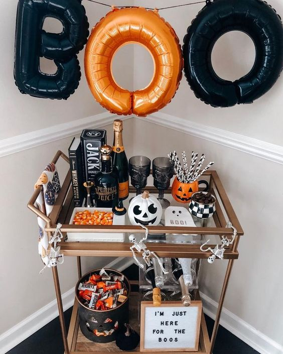 a bold Halloween bar cart with an orange and black letter garland, pumpkins, candies, an artwork and skeletons
