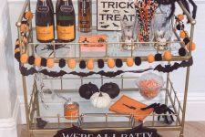 a bold Halloween bar cart with an orange and black pompom garland, black and white pumpkins, black spiders and drinks