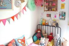 a bold kid's room with colorful art, accessories and toys, colorful bedding, pompoms and garlands
