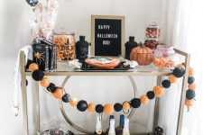 a bright Halloween bar cart with an orange and black garland, a sign, bats on the wall, pumpkins, candies and a gnome