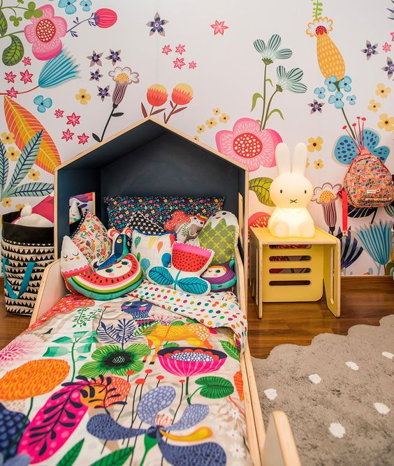 a bright and fun kid's room with a floral wall, matching floral bedding, fruit and flower pillows and a Miffy lamp