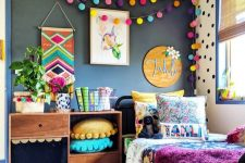 a bright kid's room with a black wall, colorful pompom garlands, pillows, bedding and a rug is extra bold