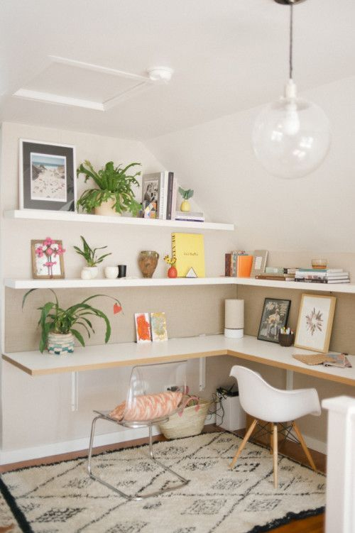 a bright shared contemporary home office with a corner desk and matching shelves, bright accessories and mismatching chairs