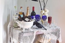 a colorful Halloween bar cart with cheesecloth, neutral pumpkins, blue glasses, a pumpkin vase with branches and a crow