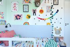 a colorful and fun kid's room with a color block wall, bright decor and garlands, colorful bedding and linens and bold toys