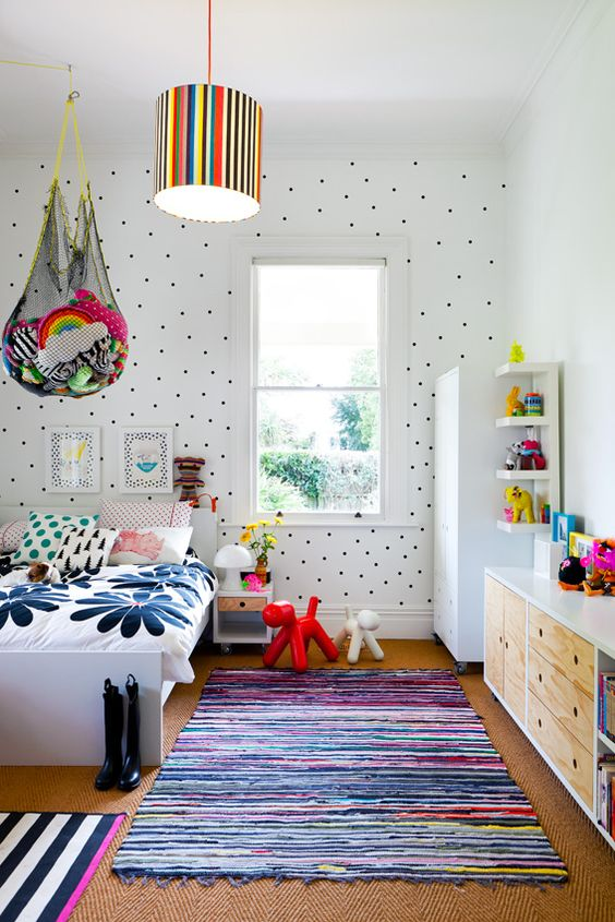 a colorful kid's room with a polka dot wall, colorful bedding and rugs, bold toys in nets over the bed