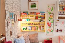 a colorful kid's room with a wallpaper wall, a yellow shelf, bright artworks and bedding and colorful toys