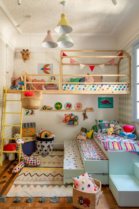 a colorful kid's room with bright bedding, rugs, pillows and blankets and pastel pendant lamps
