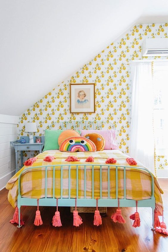 a colorful kid's room with retro fruit print wallpaper, colorful bedding, artworks, tassels and a blue nightstand
