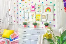 a colorful kid's space with a polka dot wall, a bold garland, bright bedding and fruit pillows and a bold rug just wows