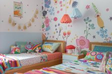 a colorful twin kid's room with a floral statement wall, colorful bedding and pillows, pendant lamps and a tassel garland