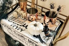 a cool Halloween bar cart with copper mugs, a crow, white pumpkins, skulls, black spiderwebs and shiny touches