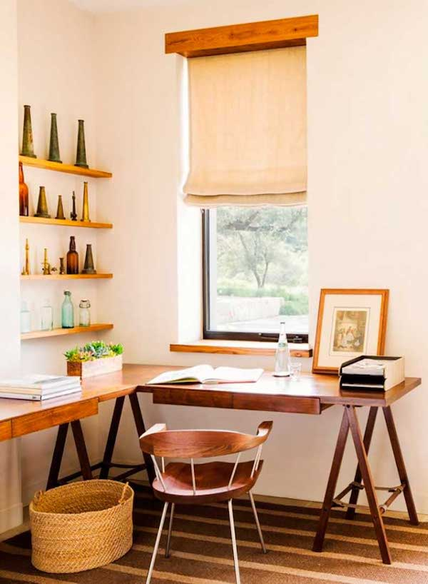a cozy rustic home office nook with a large trestle corner desk, open shelves, a basket and a wooden chair plus shades