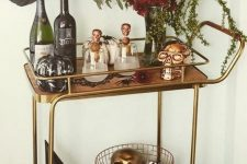 a glam Halloween bar cart with a floral centerpiece, gilded and copper skulls, pumpkins and greenery is easy and chic