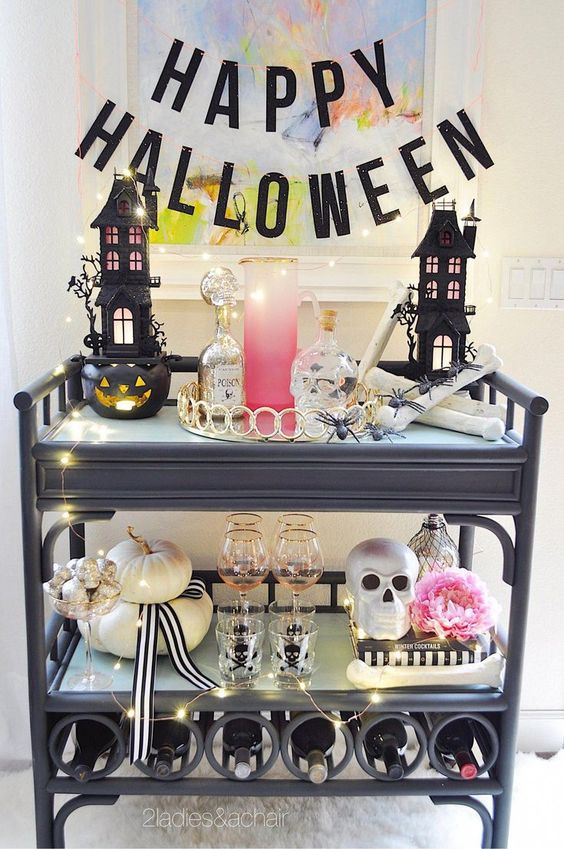 a glam Halloween bar cart with scary houses, skulls, a pink bloom, neutral pumpkins, lights and a black letter banner