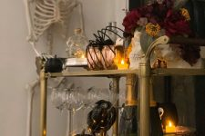 a haunted Halloween bar cart with candles, black pumpkins, a dark floral arrangement, copper mugs and spiders held by a skeleton