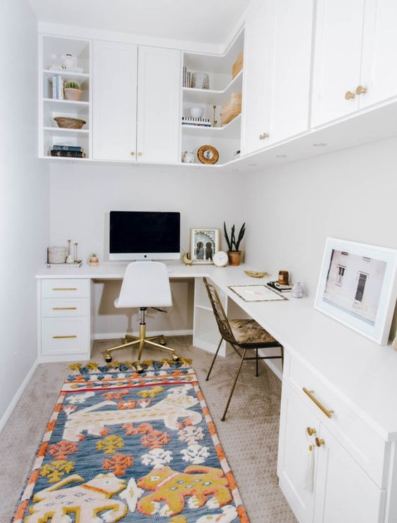 a mid century modern home office in white, with a corner desk and cabinets in it, cabinets over the desk and a bright and fun rug