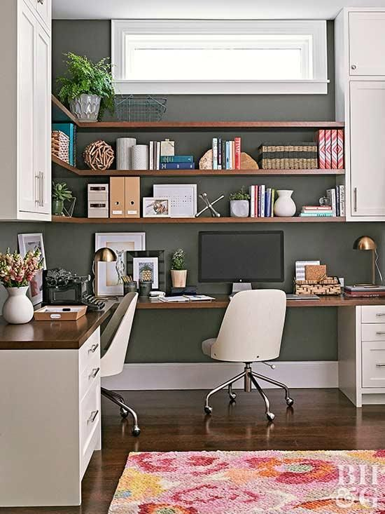 a mid century modern home office with a black wall, a corner desk and open shelves with closed storage units plus chic white chairs