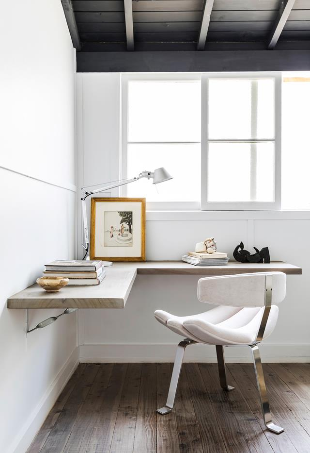 a minimalist home office nook with a floating corner desk, a whimsical chair and books and a stylish industrial lamp