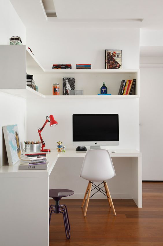 a minimalist home office with a corner desk and a corner box shelf, bright accesosries and a lamp plus a metal stool