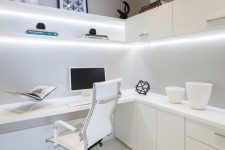 a minimalist home office with a corner desk and some storage cabinets under the surface, lit up shelves and cabinets above