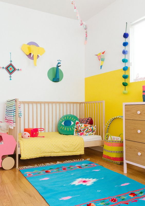 a modern colorful kid's room with a color block yellow and white wall, bright bedding and a rug, cardboard taxidermy and accessories
