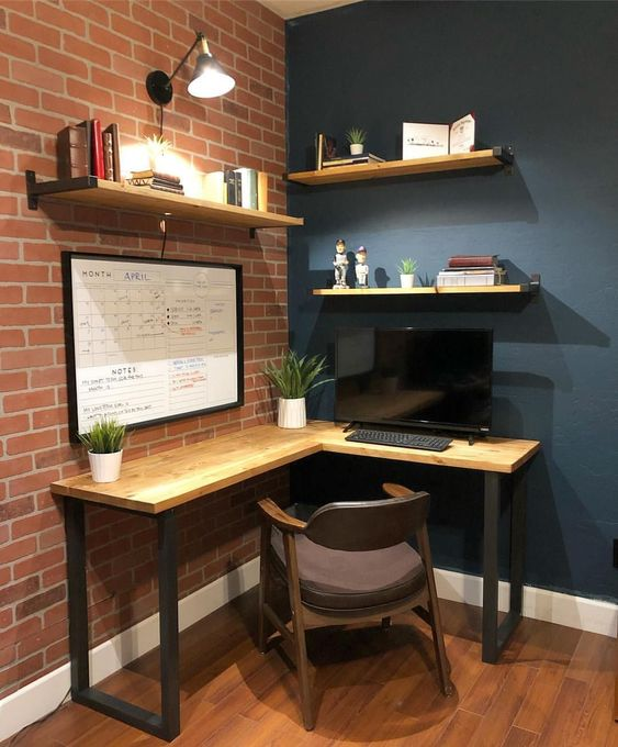 a modern industrial home office nook with a wooden corner desk and some shelves, a comfy chair and lamps