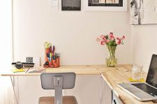 a modern industrial home office with a wooden floating desk, metal stools, a black and white gallery wall and blooms