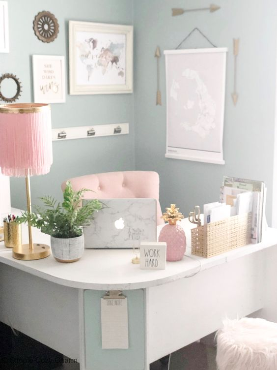 a pastel girlish home office with a curved corner desk, pink accessories and a pink chair and gold touches for more chic
