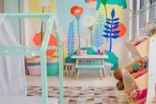 a pastel kid's room with a bright floral wall, a mint house-shaped bed, colorful toys and a bold rug and baskets