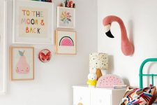 a pastel kid's room with pastel artworks, faux taxidermy, bright bedding and a bold green bed
