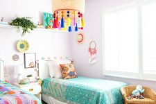 a pastel shared kids' bedroom with lavender walls and a pouf, colorful bedding and art and a lamp with colorful tassels