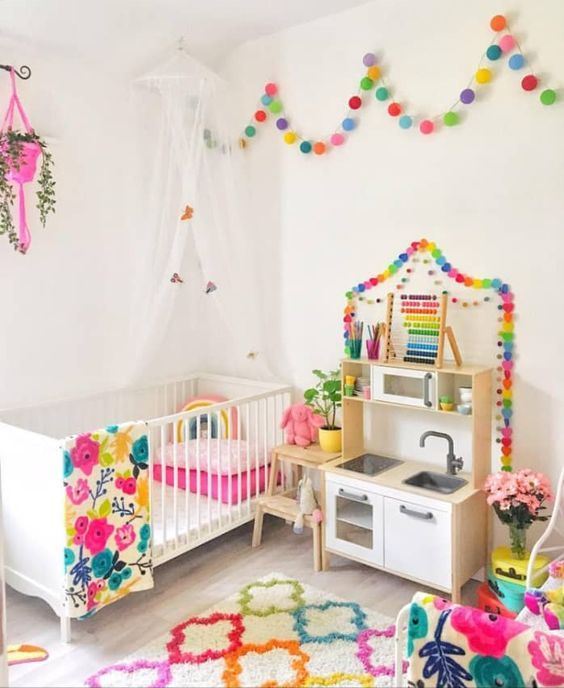 a rainbow splashed kid's room with colorful garlands, a bold rug, colorful bedding and a hot pink planter