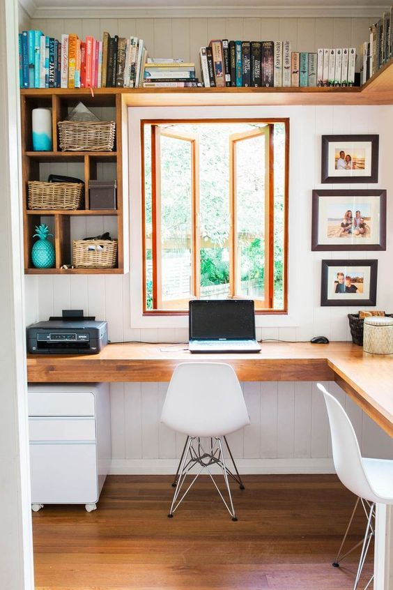 a rustic modern home office with a wooden corner desk, open shelves, white chairs and lots of books and photos