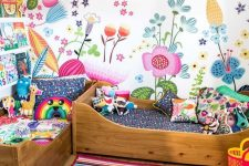 a shared colorful kid's room with a bright floral wall and bold bedding, a bold striped rug and books on the bookshelves