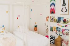 a shared kid's room done in neutrals but spruced up with brights – polka dots on the wall, colorful art, garlands and books