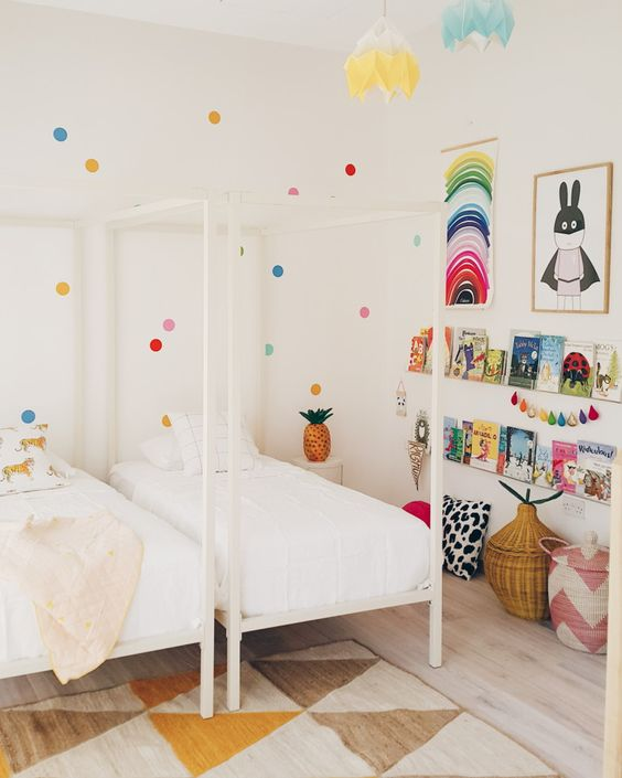 a shared kid's room done in neutrals but spruced up with brights - polka dots on the wall, colorful art, garlands and books