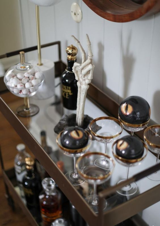 a spooky Halloween bar cart with a skeleton hand, scary eyeballs in glasses and gold touches here and there
